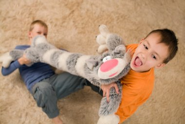 Two kids with a toy cat on the floor