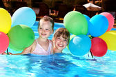 Photo Kids playing with balloons in swimming pool.