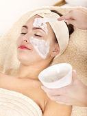 Fotografie Kosmetikerin trägt Gesichtsmaske von Frau auf.
