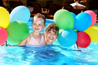 Kids playing with balloons in swimming pool.