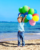 Photo Child playing with balloons at the beach