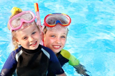 Kids in swimming pool learning snorkeling.