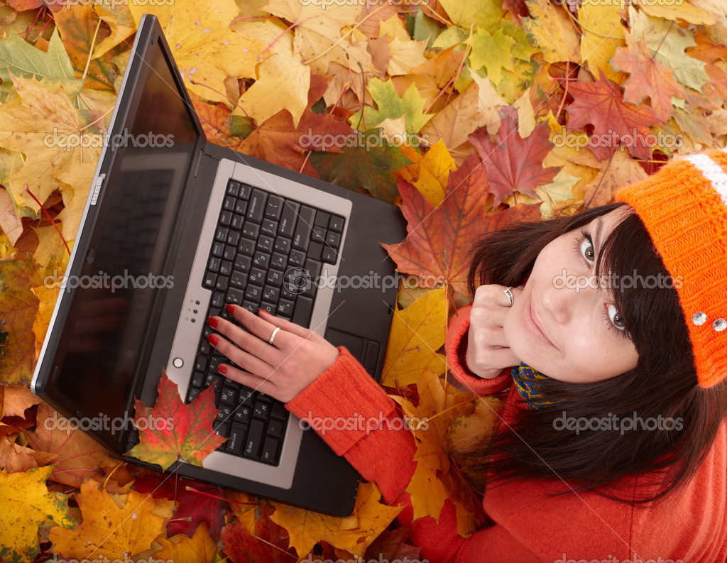 Girl in autumn orange foliage with laptop.
