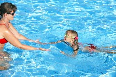 Swimming instructor learn child swim.