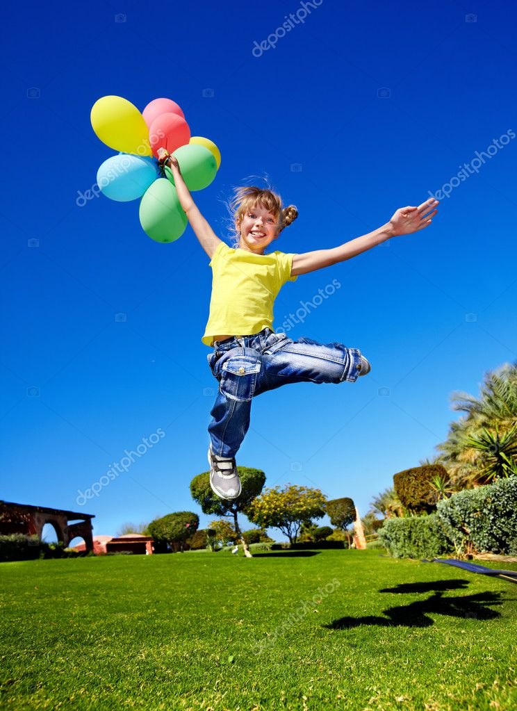 Child playing with balloons in park.