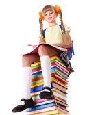 Photo Schoolgirl sitting on pile of books.