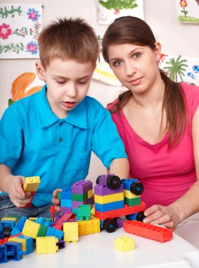 Child playing lego block with mother at home.