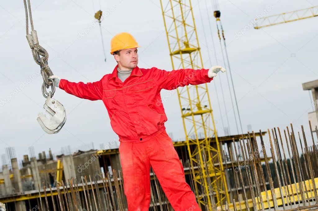 b4a03e4fc2558 Constructor de Montador en uniforme y casco de funcionamiento con las  correas en el área de la construcción — Foto de kalinovsky