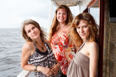 Three beautiful young women a Caucasians standing together on the deck of y
