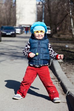 Little child with lollipop is standing outdoors. Funny glasses