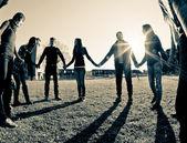 Fotografia giovane multirazziale, tenendosi per mano in un cerchio
