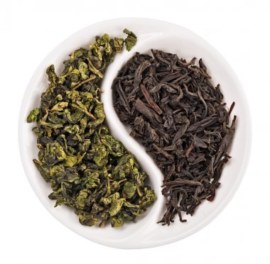 Green leaf tea versus black one in Yin Yang shaped plate, isolat