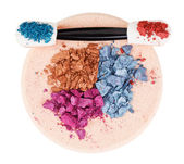 Fotografie Heap of broken multicolor eyeshadow over makeup sponge, isolated