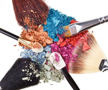 Composition with makeup brushes and broken multicolor eye shadow