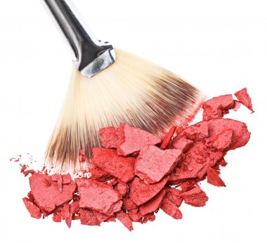 Makeup brush with red crushed eye shadow, isolated on white macr