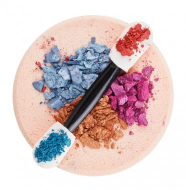Heap of broken multicolor eyeshadow over makeup sponge, isolated