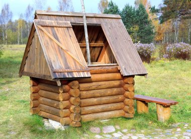 Wooden well stylised semi-antique against a rural landscape