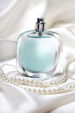 Blue perfume bottle and pearl necklace on the white silk background