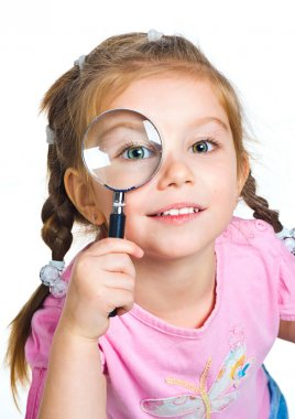 Little girl looking through a magnifier