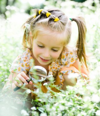 Little girl with magnifying glass looks at flower