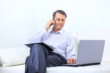 Entrepreneur working from home looking very relaxed in his sofa browsing th