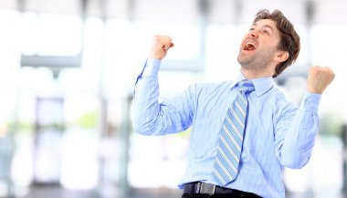 Portrait of an energetic businessman with his arms raised