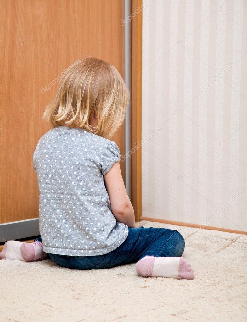 A sad girl is sitting on the floor