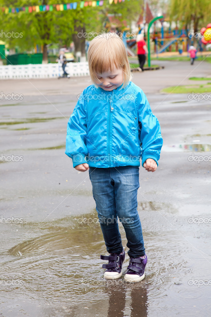A girl is jumping in the puddle