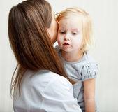 eine Mutter hält ein krankes Mädchen