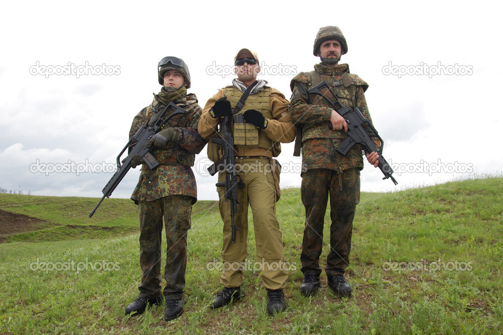 Three soldiers outdoors posing