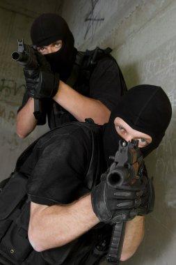 Soldiers in black masks targeting with AK-47 rifles