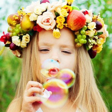 Little girl with wreath from flowers blows soap bubbles stock vector