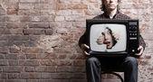 TV-vel és a lány képe-szemben egy lyuk a kezében egy ülés