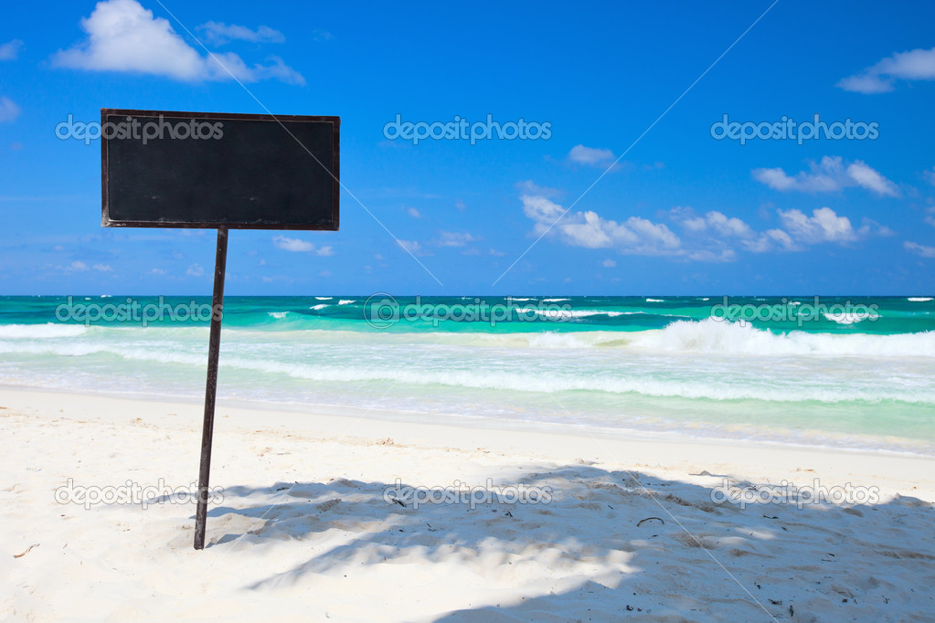 Blank blackboard display on tropical beach