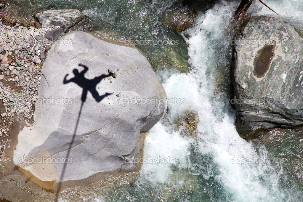 Falling bungee jumper shadow above mountain river