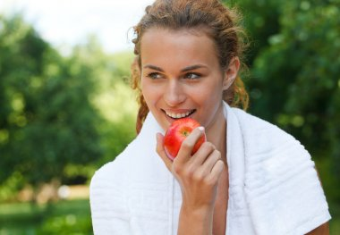 Young woman after sport workout eating apple