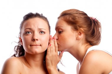 Young woman whispering something to her frind.