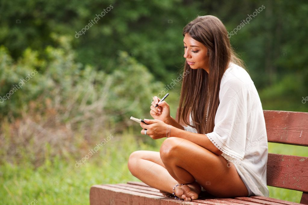 Beautiful woman writing in a small book