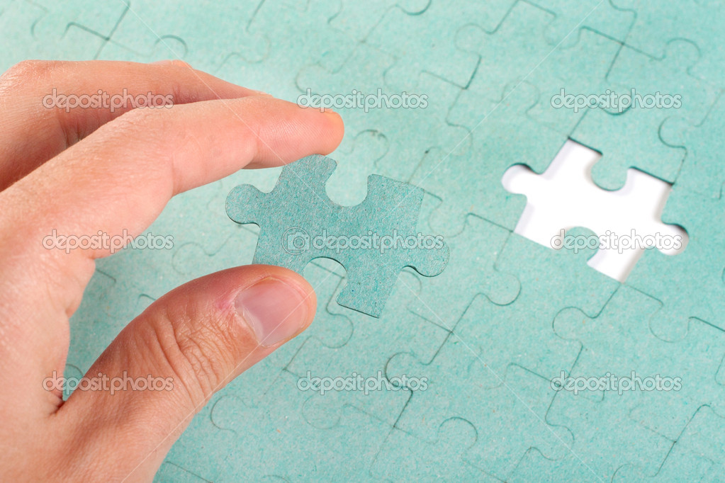 Hand Inserting Missing Piece Of Green Jigsaw Puzzle Into The Hol Stock Photo