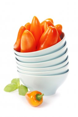 Stack of bowls and fresh orange peppers over white stock vector
