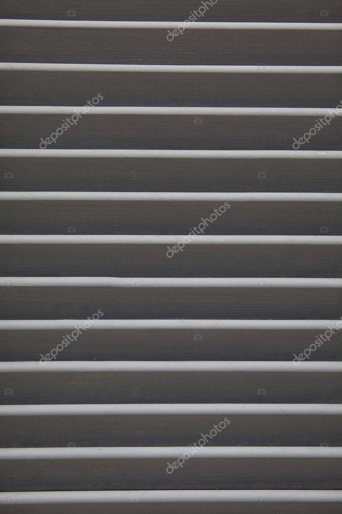 Grey shutters over a shop doors