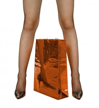 Female legs and red shopping bag