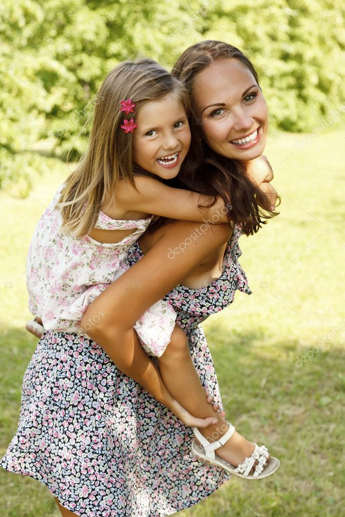 Mother giving daughter piggy back ride at summer park