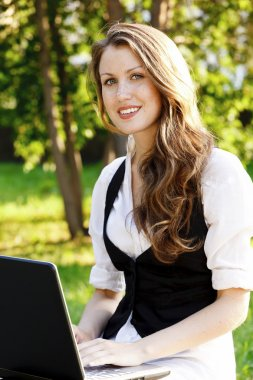 Young pretty woman with laptop sitting on the bench in a park