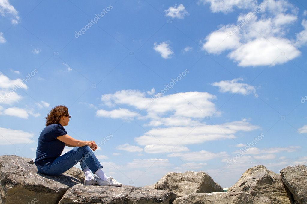 Meditating sixty year old mature woman sits on rocks and gazes out into a cloudy blue sky.