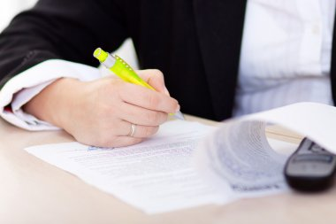 Hand of the businesswoman writing note (hand with pen in focus)