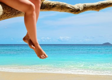 Sand beach, azure sea and woman legs