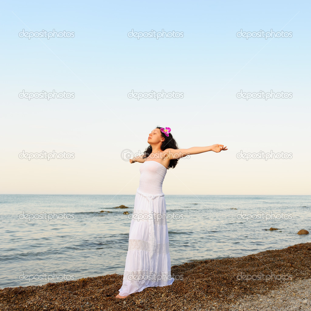 The woman in a white sundress on seacoast with open hands