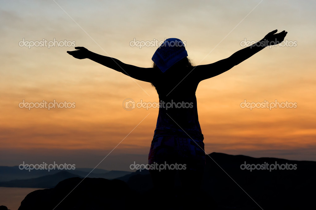 The woman on a mountain with open hands welcomes a decline