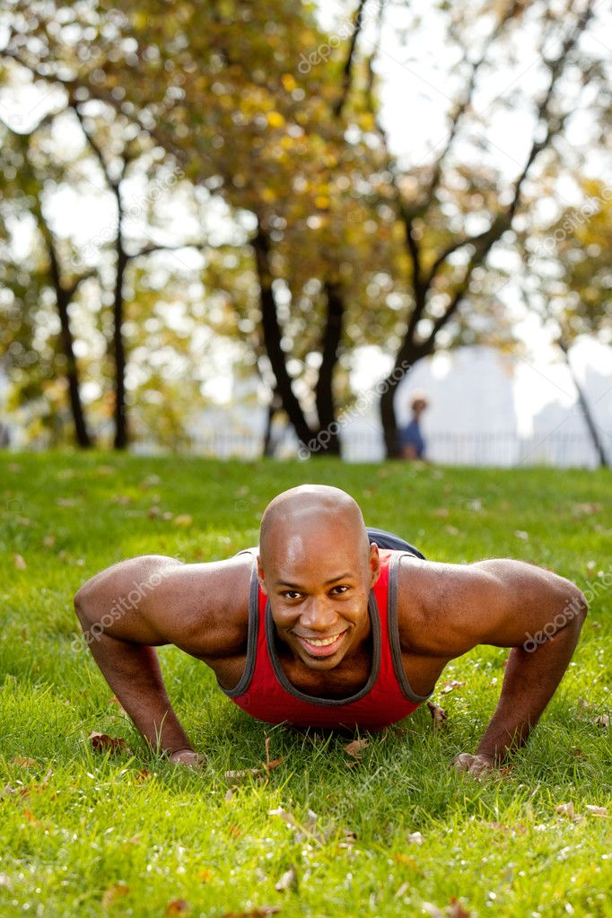 An african american doing push ups in the park